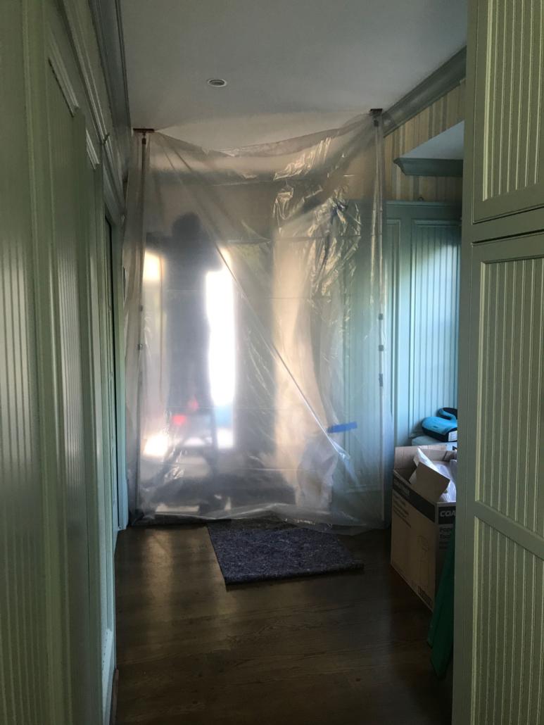 Door Store installer behind plastic sheeting.