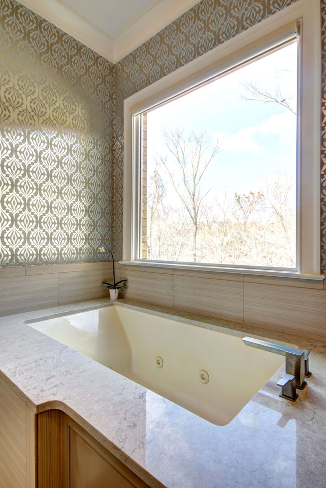 a picture window over a marble bathtub