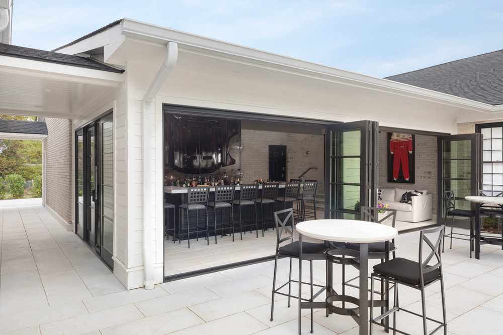 garage turned bar with bi-fold doors open to the patio