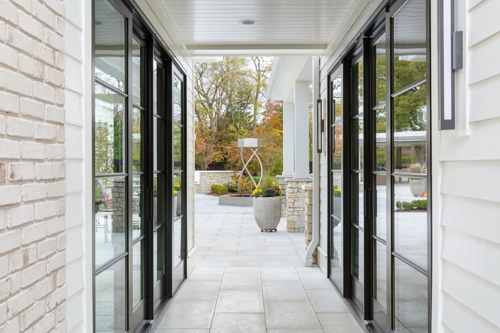 two mirroring black sliding french doors in a covered breezeway