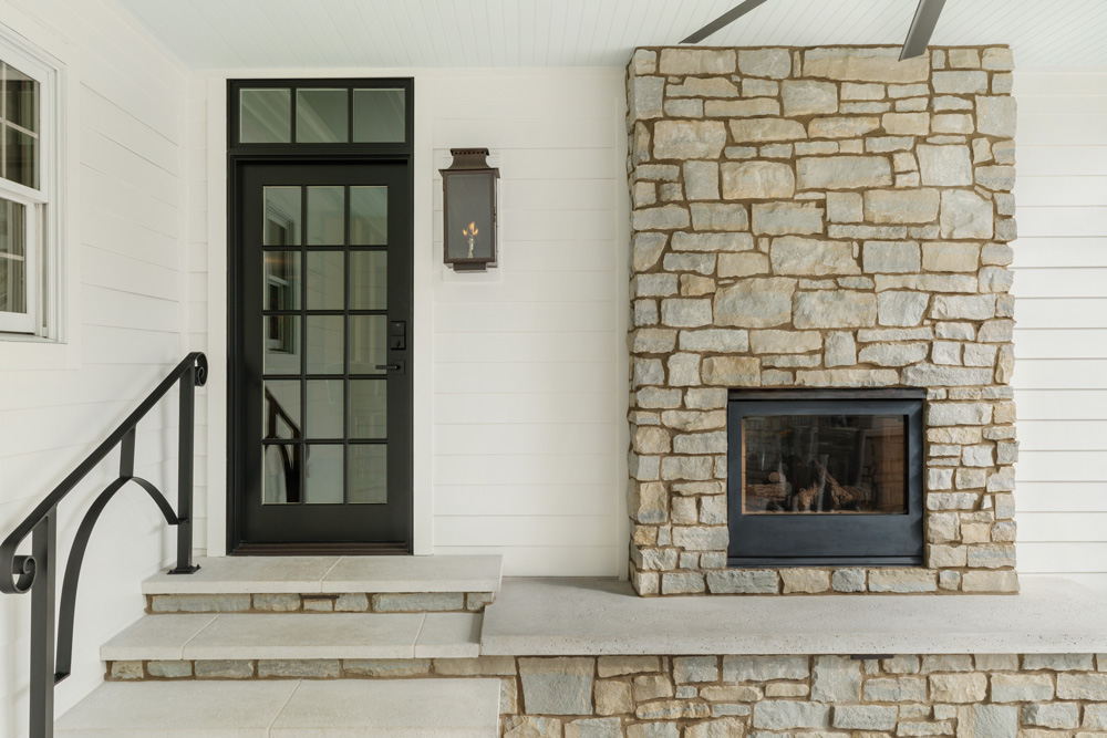 black single french exterior door with transom next to a stone fireplace