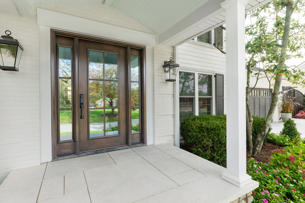 Dark wood front door with six panes and sidelites on white house