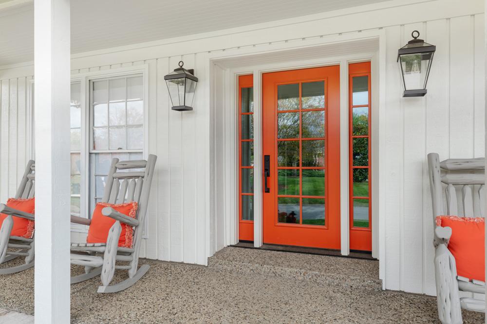 bright orange door on white house. white rocking chairs with matching orange pillows